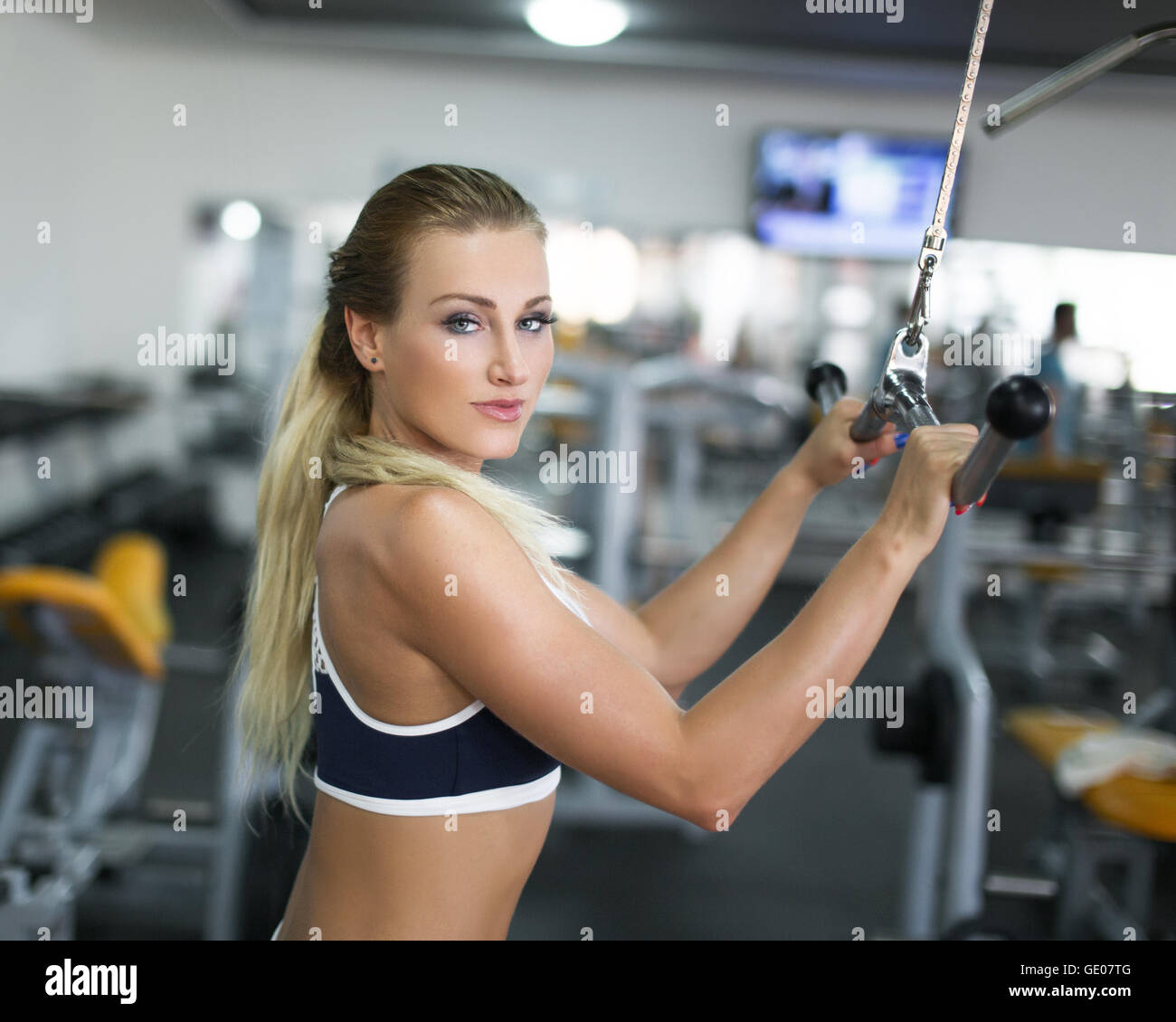 Woman doing exercise on triceps machine in gym Stock Photo