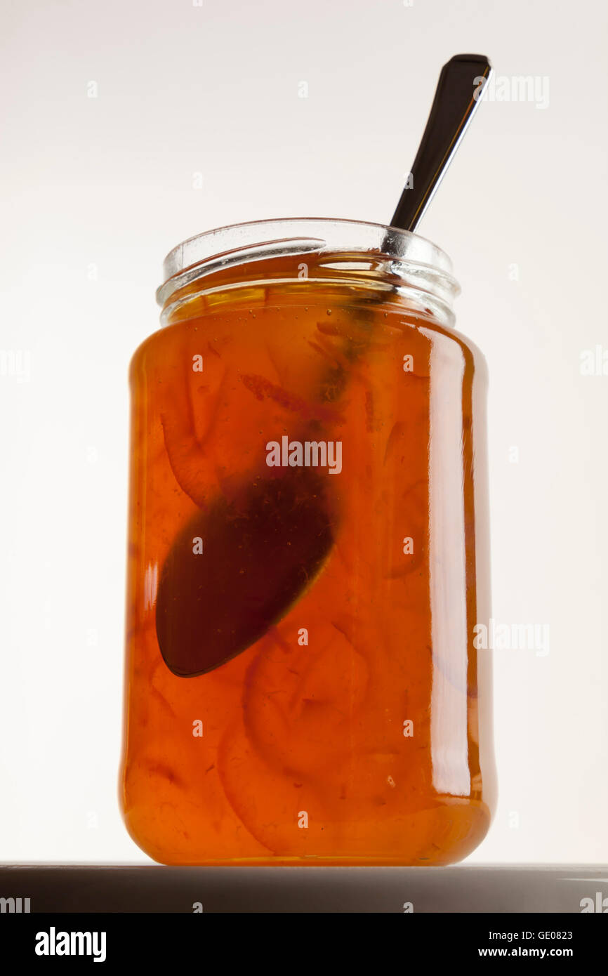 Jar of orange marmalade and spoon - Stock Image