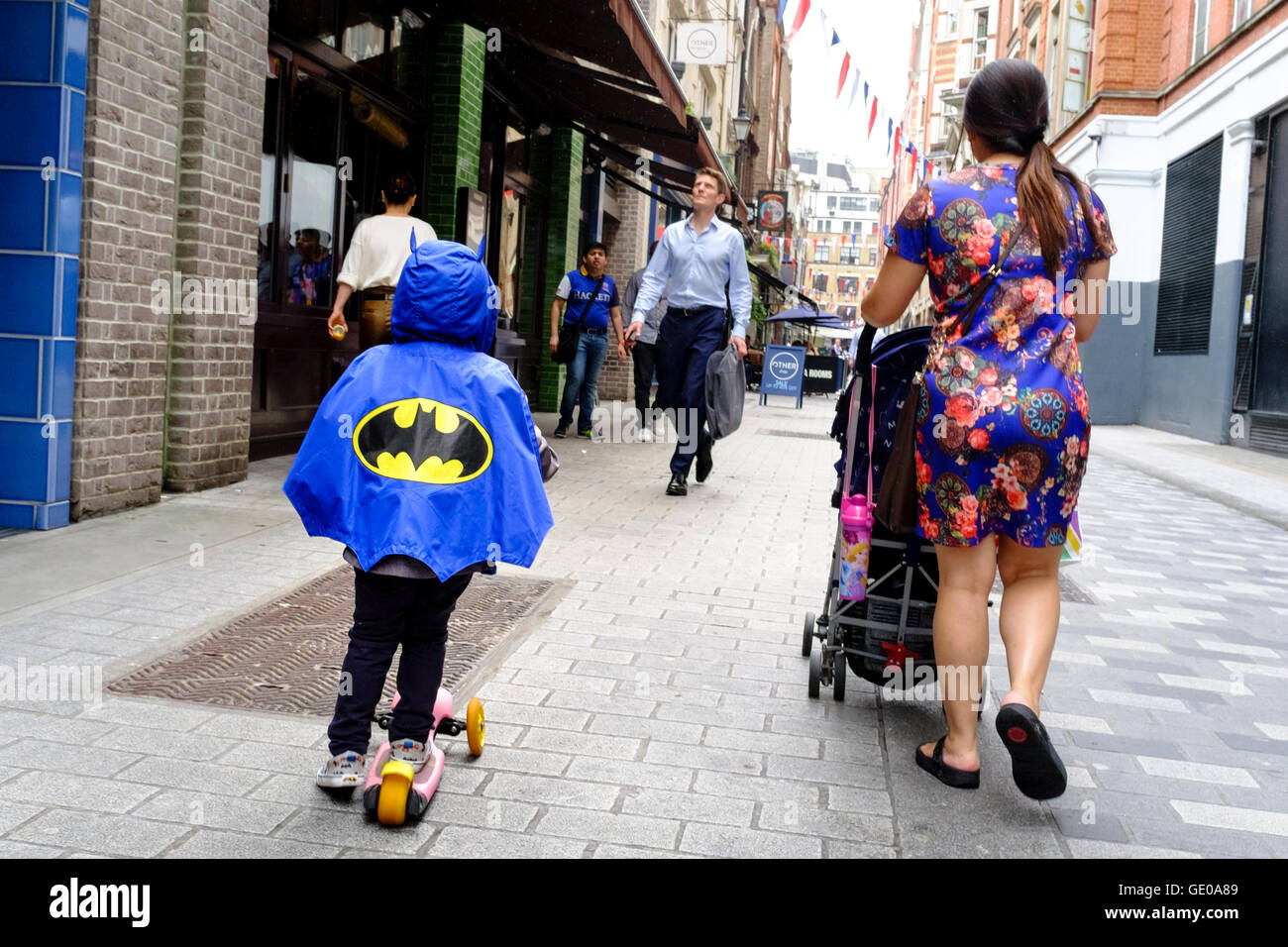 Child dressed in Batman cape accompanied by his mother pushing baby carriage in London street. - Stock Image