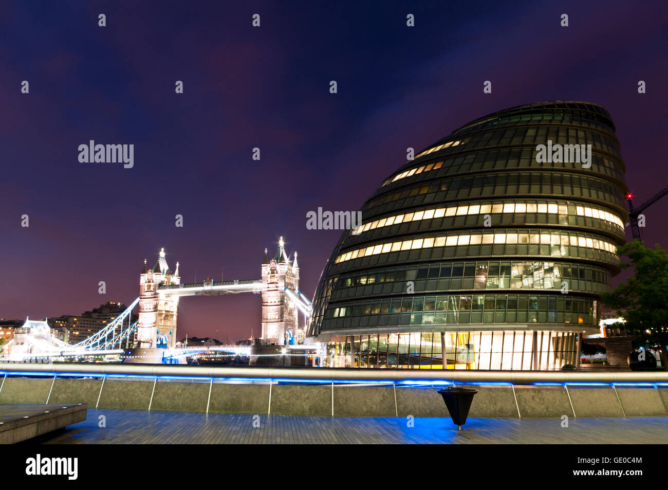 Night time view of the GLC building with Tower Bridge in the background, London England - Stock Image