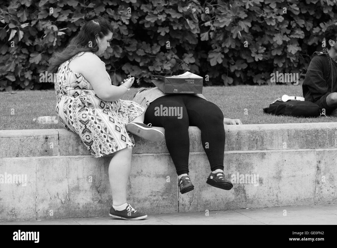 Two women relax in Trafalgar Square, London, England. One looking at her mobile device, a shopping bag resting on - Stock Image