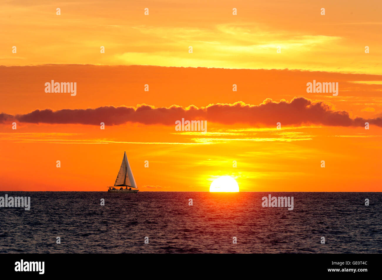 Sailing sunset is a sailboat moving along the water as the sun is going down on the ocean horizon. - Stock Image