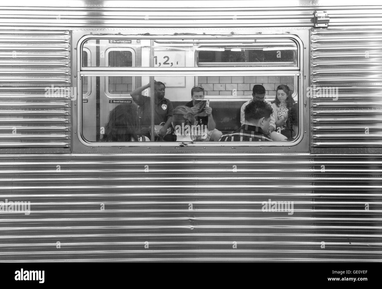 People sitting in a subway car seen through window on station Jay Street MetroTech. - Stock Image