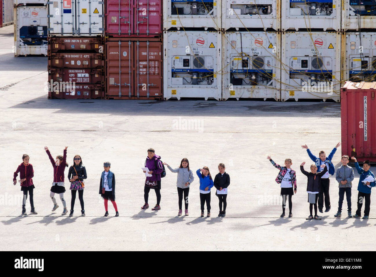 Local Greenlandic Inuit school children wave to a visiting cruise ship from the quay. Sisimiut, Qeqqata, West Greenland - Stock Image