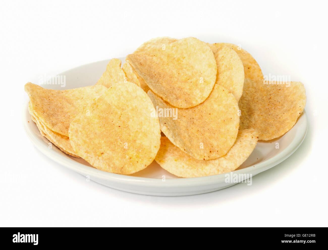 crunchy potato chips on white dish. - Stock Image