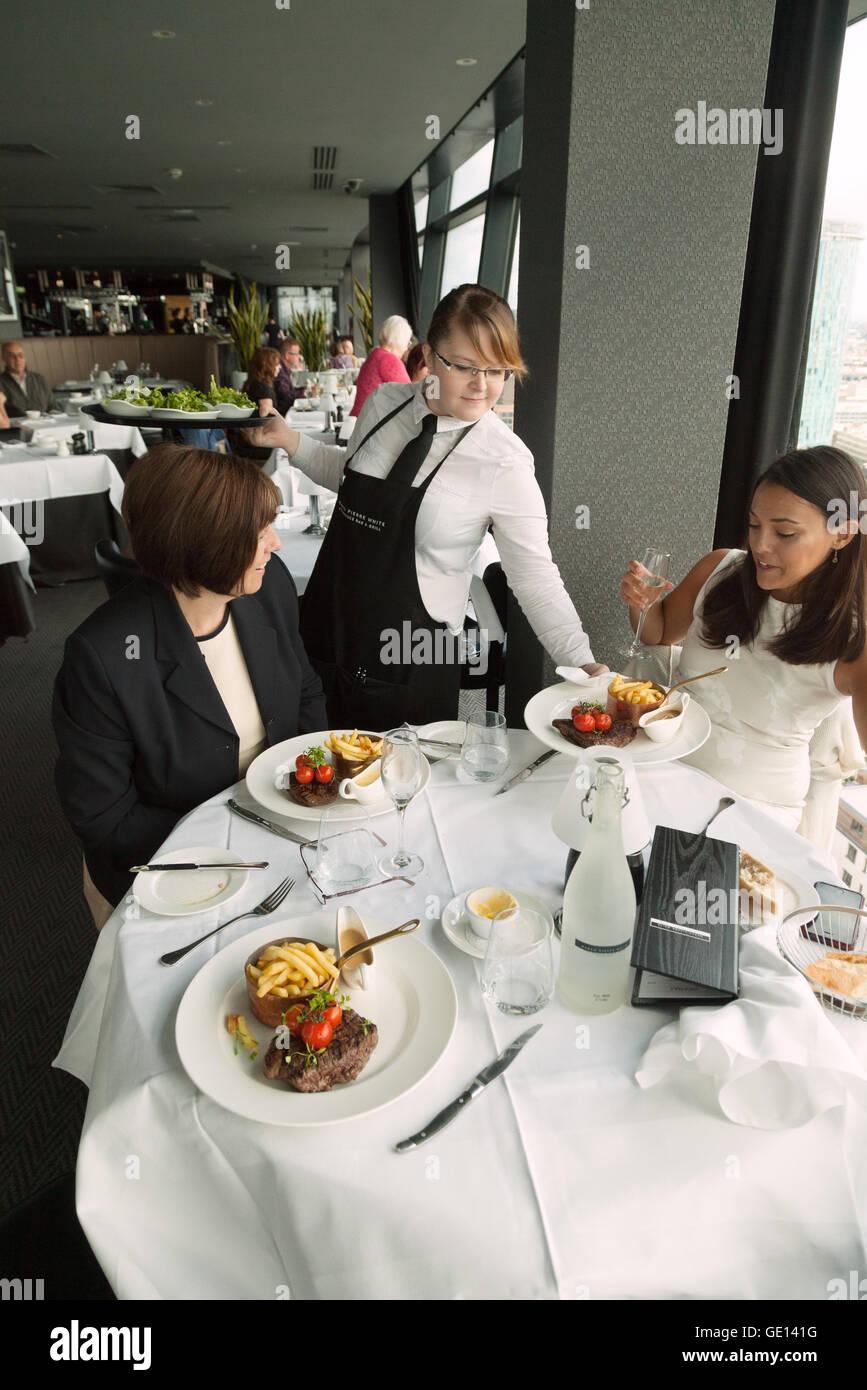 Waitress serving food, Marco Pierre White restaurant steak house, the Cube, Birmingham UK - Stock Image