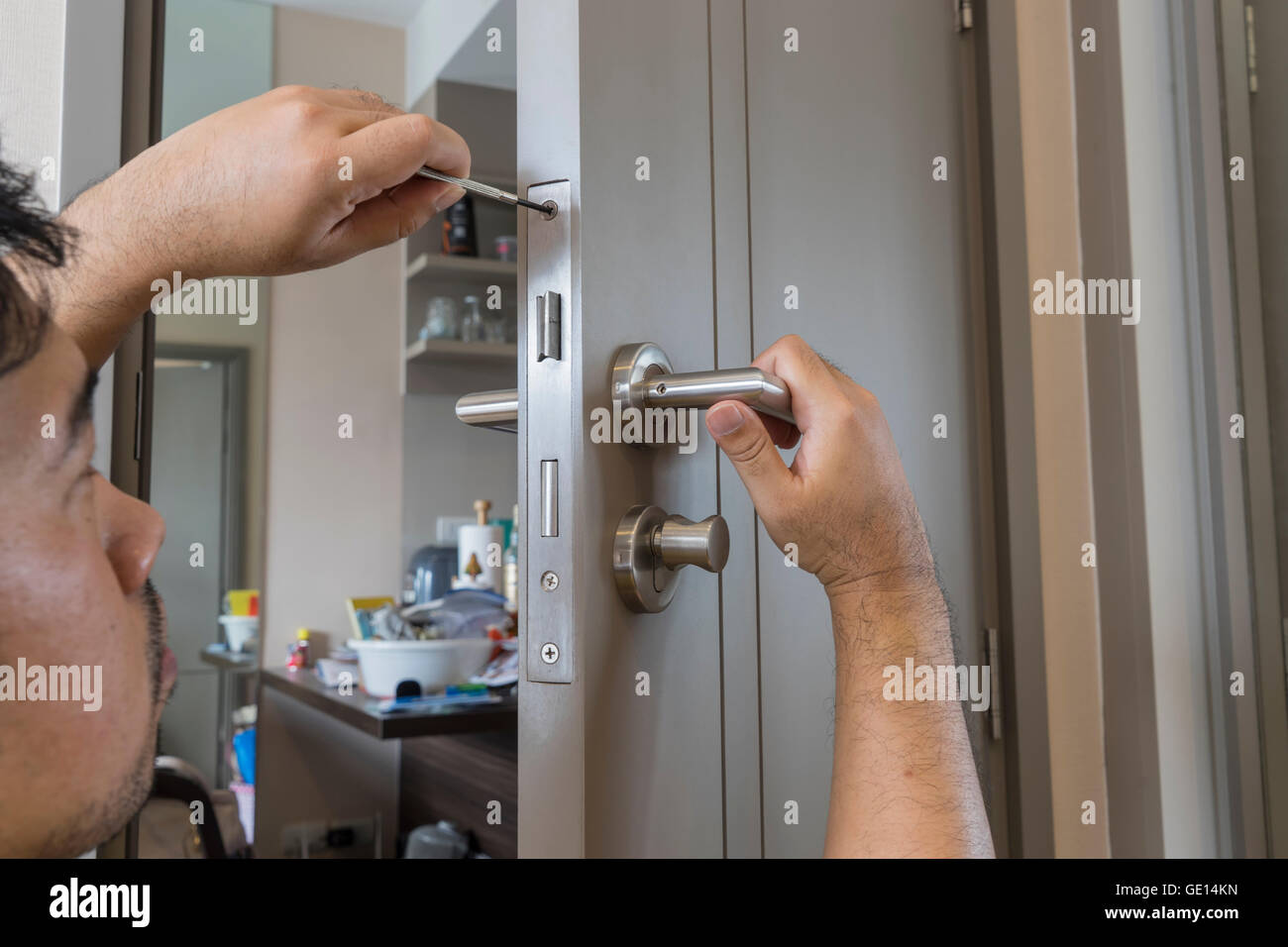 locksmith try to fix modern knob door by screwdriver - can use to display or montage on products - Stock Image