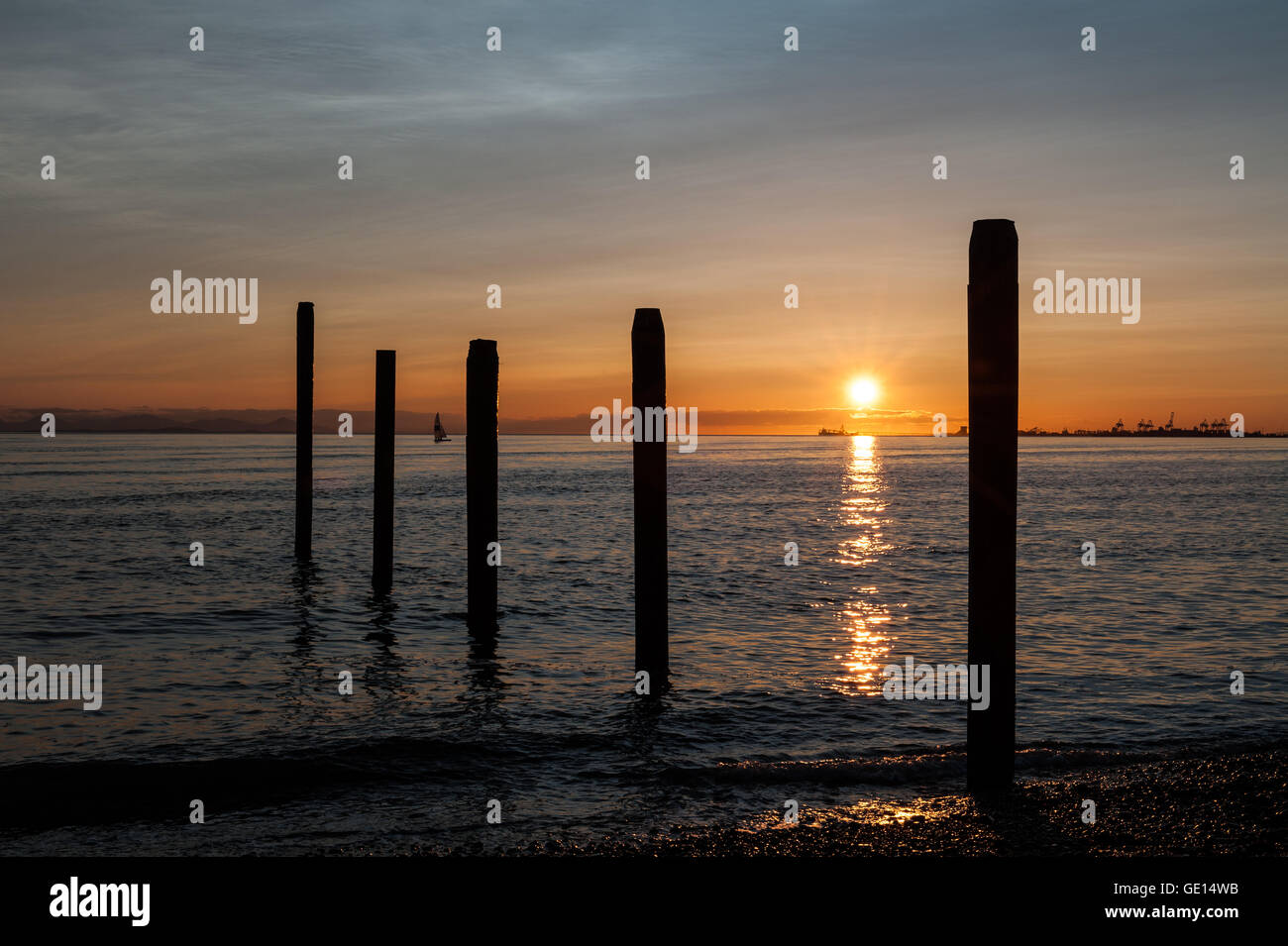 sail boat on the Pacific ocean at sunset in Point Roberts, with posts on foreground, Washington state, USA - Stock Image