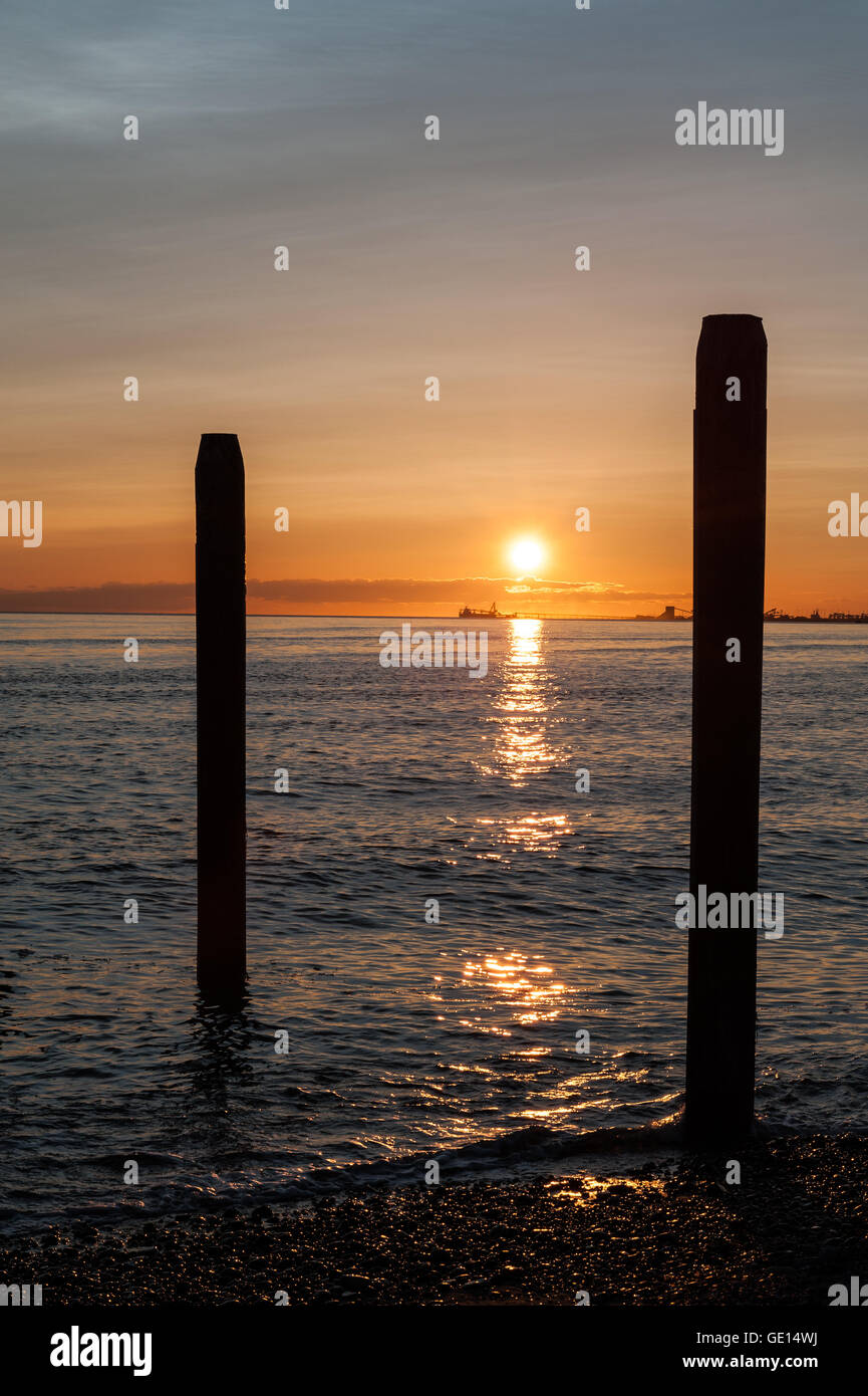 sunset over the Pacific ocean in Point Roberts, with posts on foreground, Washington state, USA - Stock Image