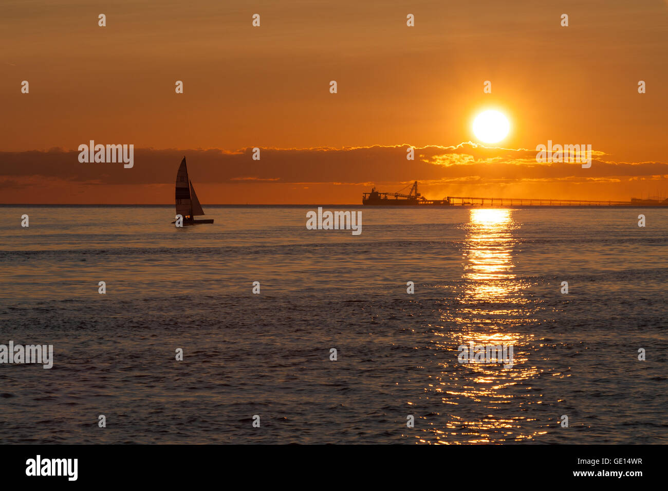 sail boat and ship silhouette at sunset on Pacific ocean at Point Roberts, Washington state, USA - Stock Image