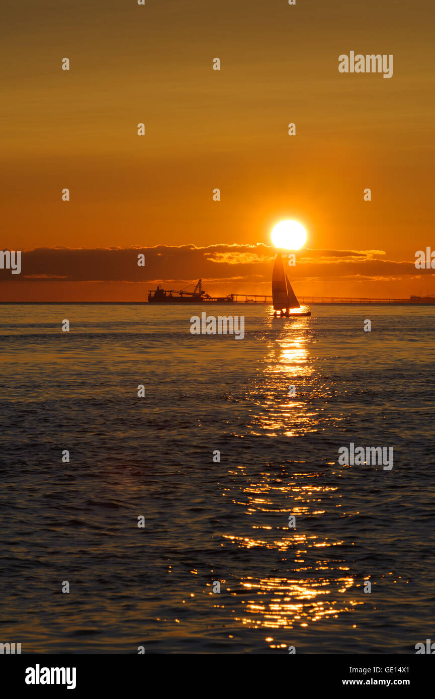 sail boat and ship at sunset on Pacific ocean at Point Roberts, Washington state, USA - Stock Image
