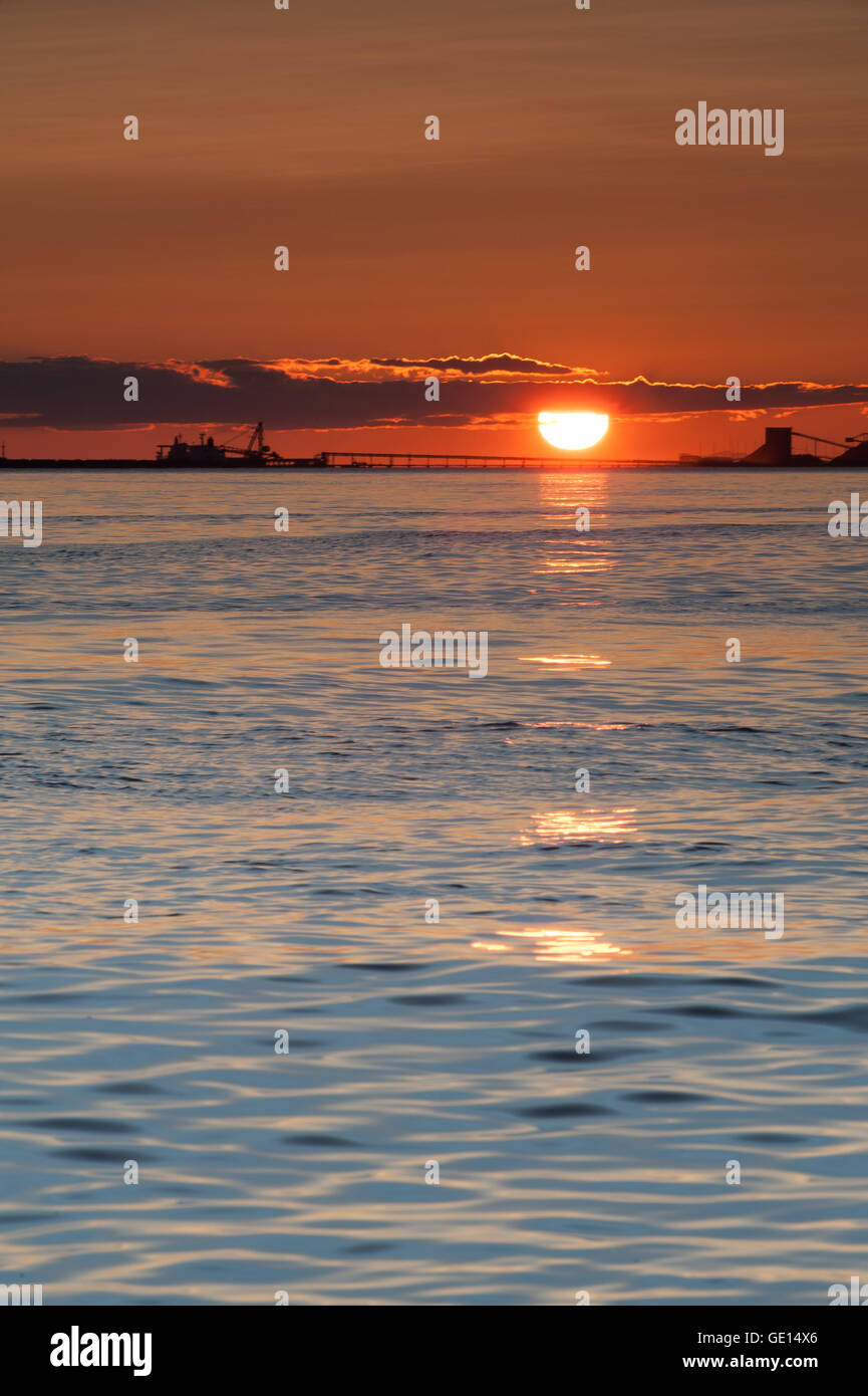 ship and cranes silhouette at sunset on Pacific ocean at Point Roberts, Washington state, USA - Stock Image