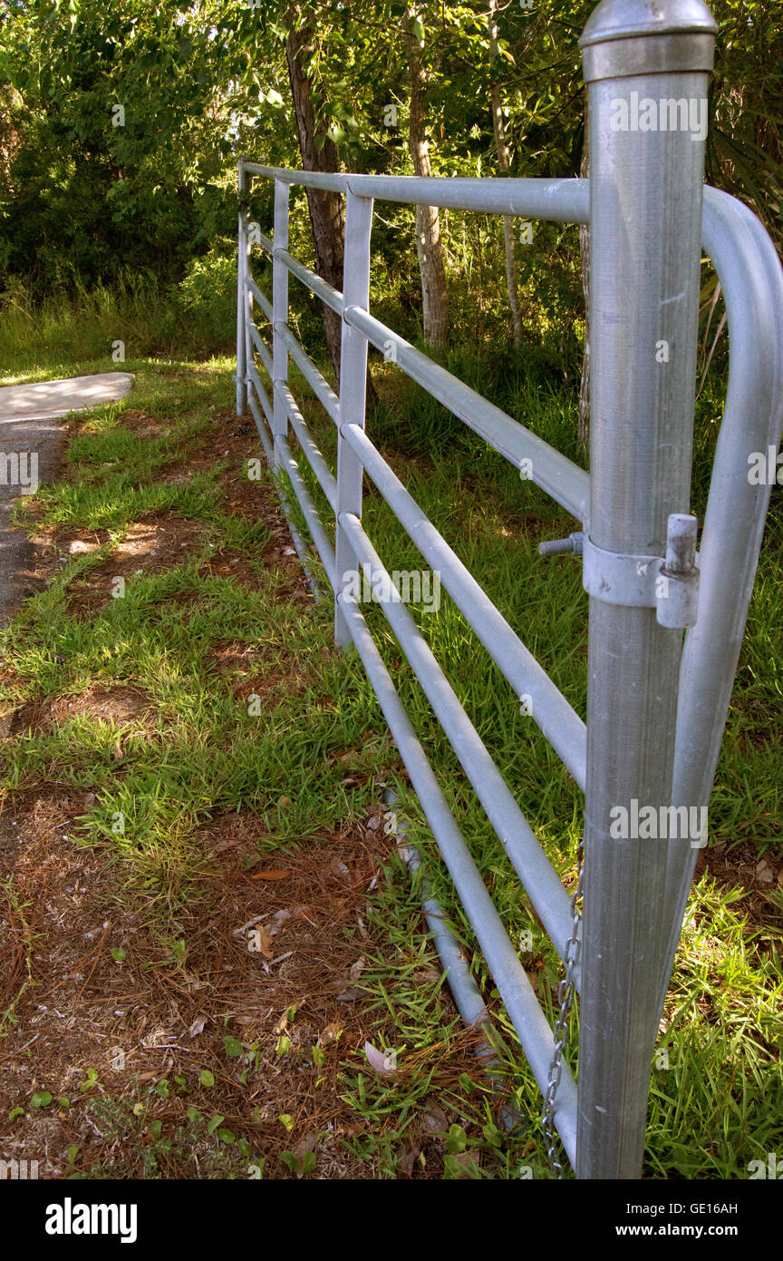 A metal post and a metal on a background of pavement, grass, and foliage. - Stock Image