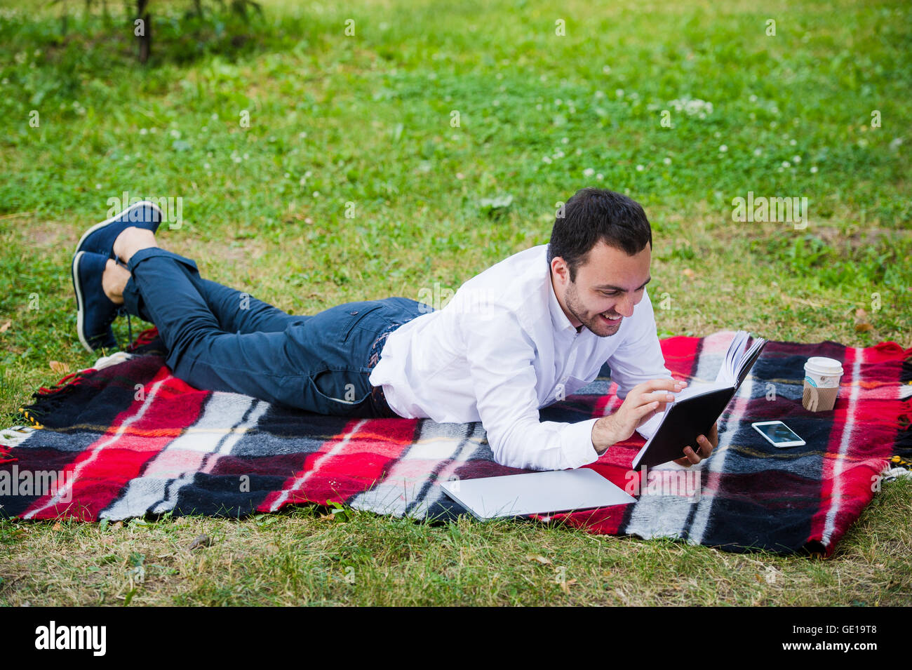 Young business man reading book outside in a park - Stock Image