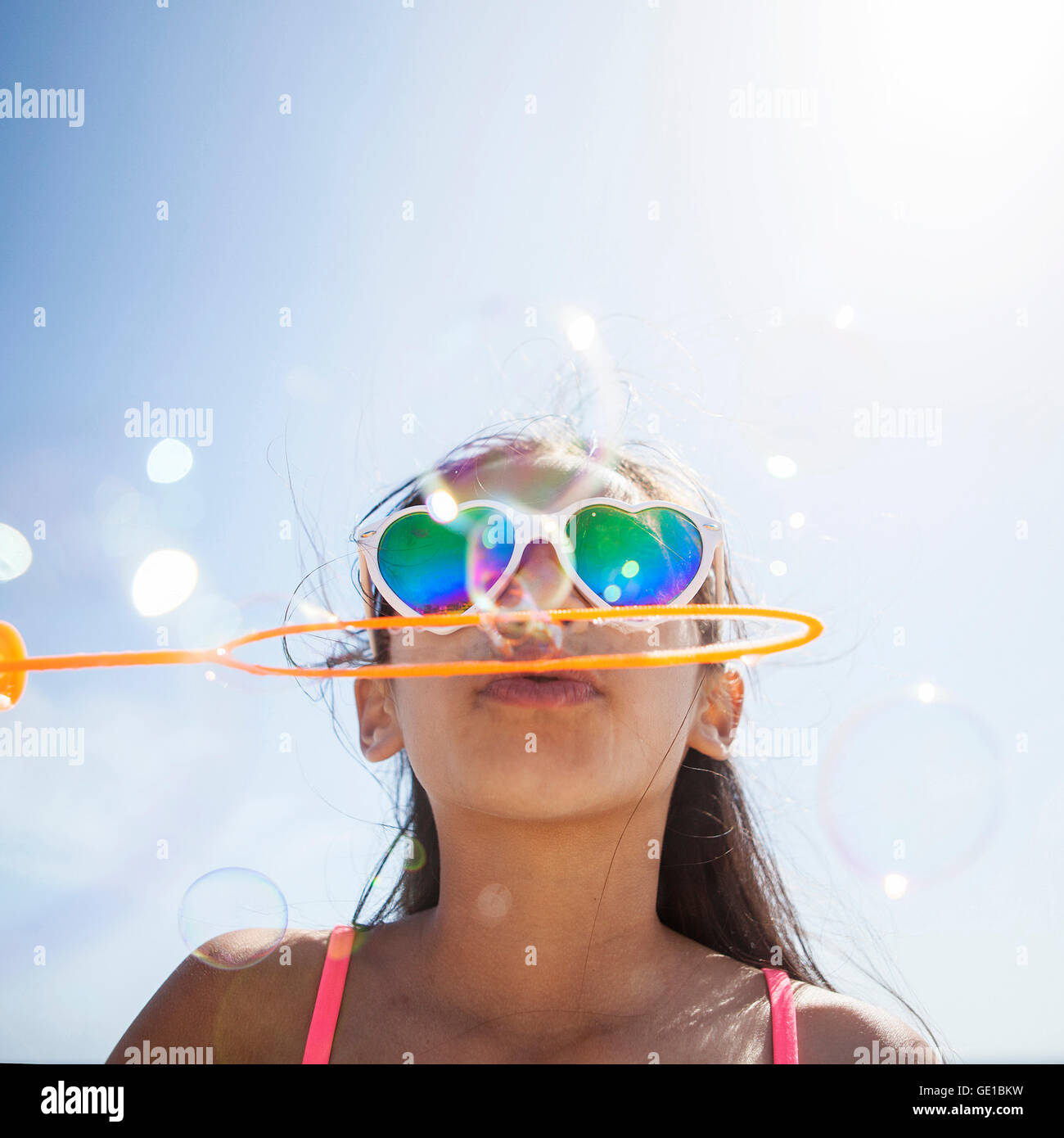 Girl in heart shaped sunglasses on beach blowing bubbles with bubble wand - Stock Image