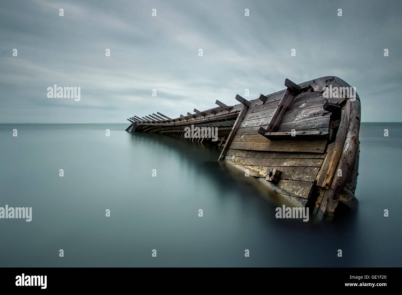 Shipwrecked boat in sea - Stock Image