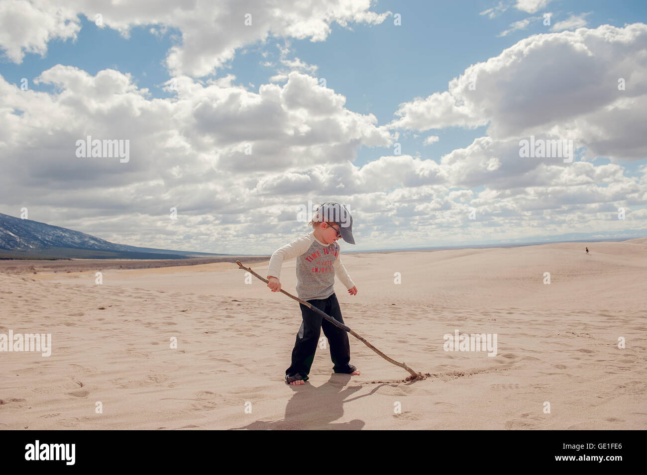Boy writing in sand with stick, Grand Sand Dunes National Park, Colorado, America, USA - Stock Image
