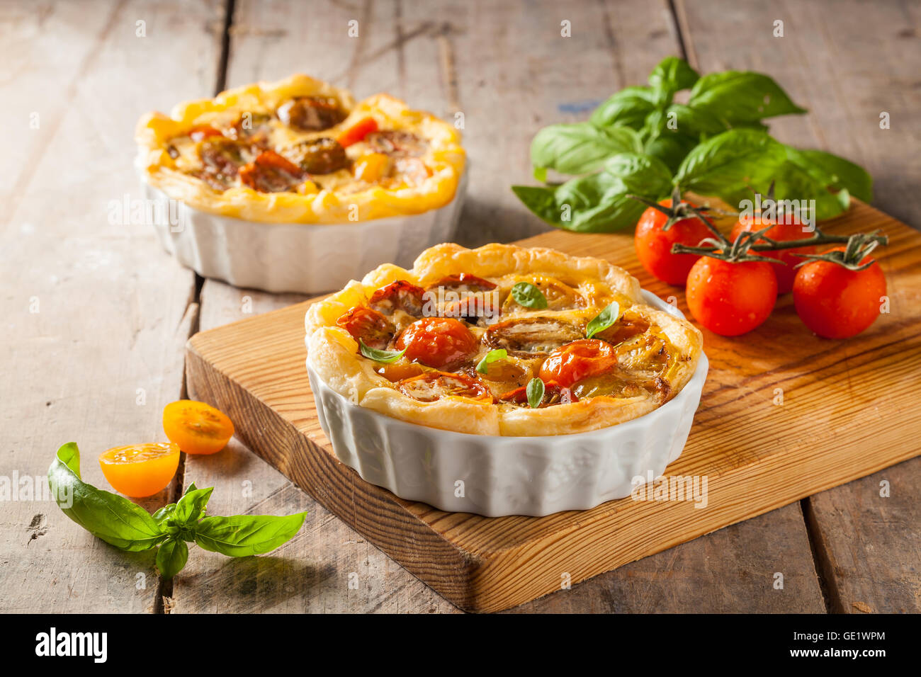 Quiche with cherry tomatoes on a rustic wooden table. - Stock Image