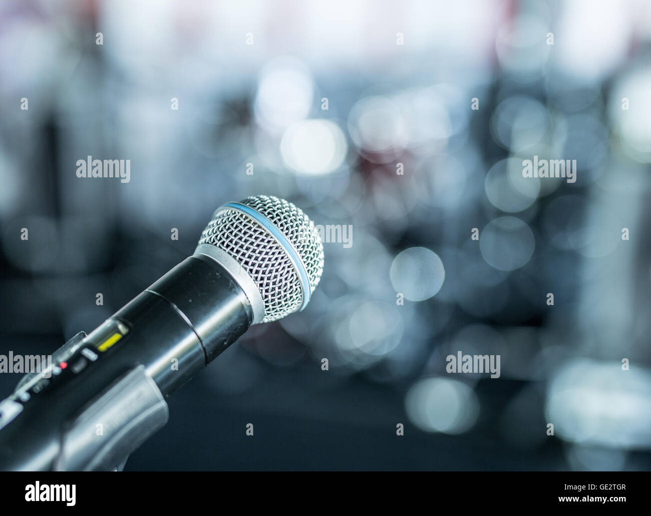 Closeup shot of microphone. Blurred lights on the background. - Stock Image