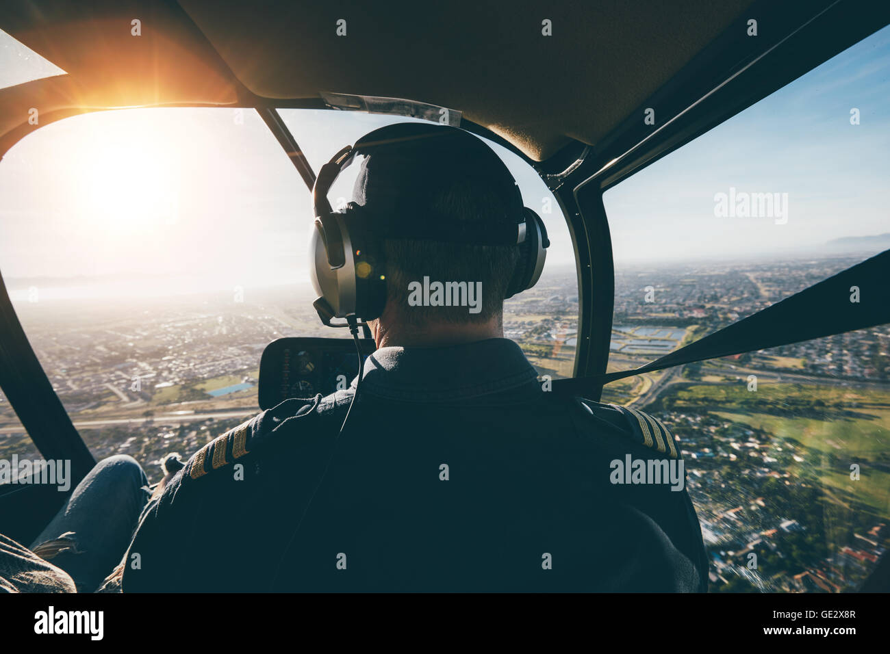 Rear view of a male pilot flying a helicopter on sunny day. - Stock Image