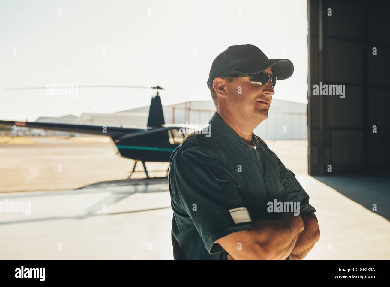 Portrait of helicopter pilot in uniform standing with his arms crossed and looking away with a helicopter in background - Stock Image