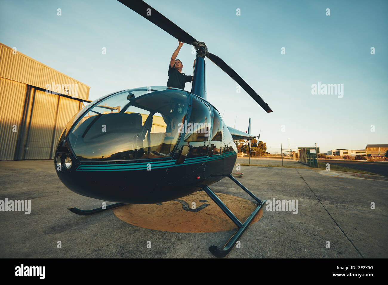 Image of pilot checking the helicopter rotor blades at the airfield. Man inspecting his aircraft before a flight. - Stock Image