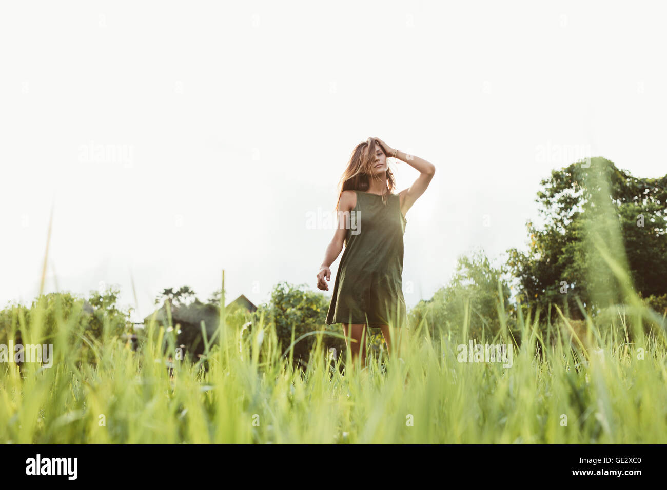 Portrait of beautiful young woman standing outdoors. Female fashion model posing outdoors. - Stock Image