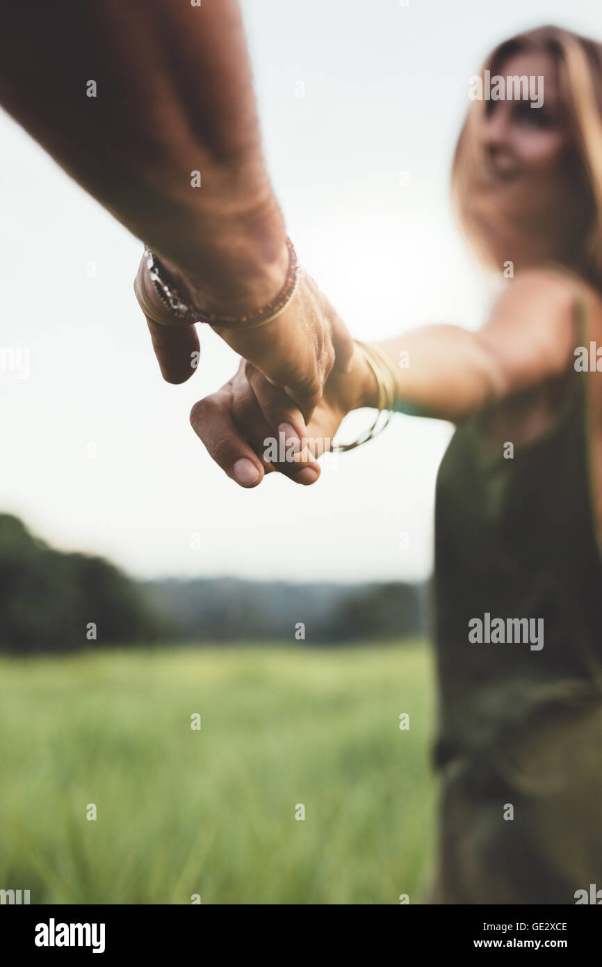 Close up shot of man holding hand of his girlfriend in grass field. POV shot of couple in nature. - Stock Image