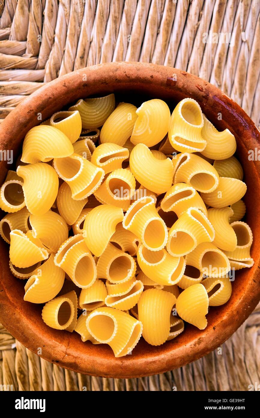 Uncooked Conchiglie pasta shells in a bowl - Stock Image