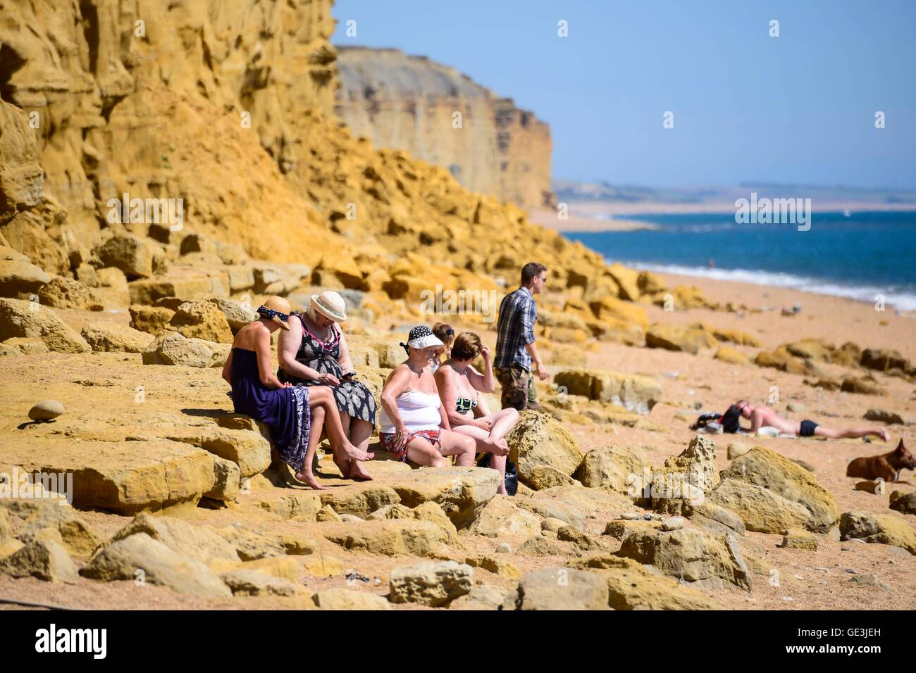 West Bay, Dorset, UK. 22nd July 2016. Holidaymakers who are unaware of the danger, sitting close to the base of - Stock Image
