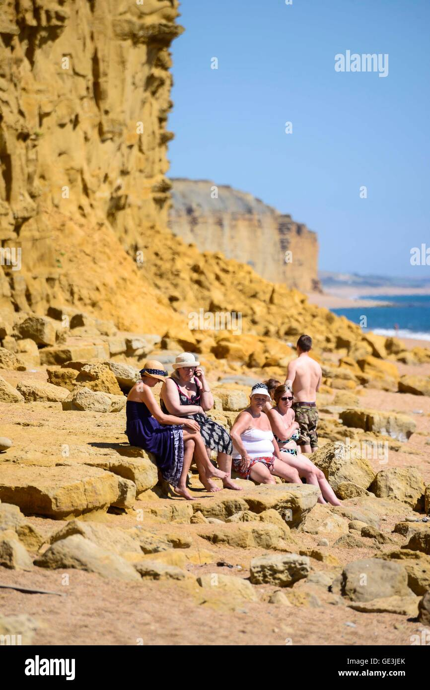 West Bay, Dorset, UK. 22nd July 2016. Holidaymakers who are unaware of the danger, sitting close to the base of Stock Photo