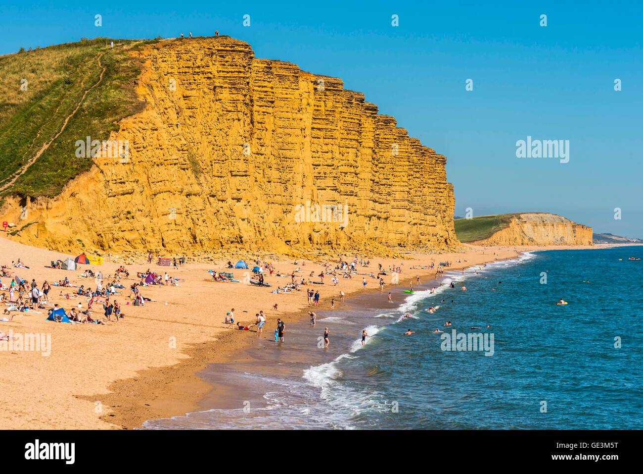 West Bay, Dorset, UK. 22nd July 2016.  UK Weather.  Wall to wall sunshine and blue sky above holidaymaker crowed - Stock Image