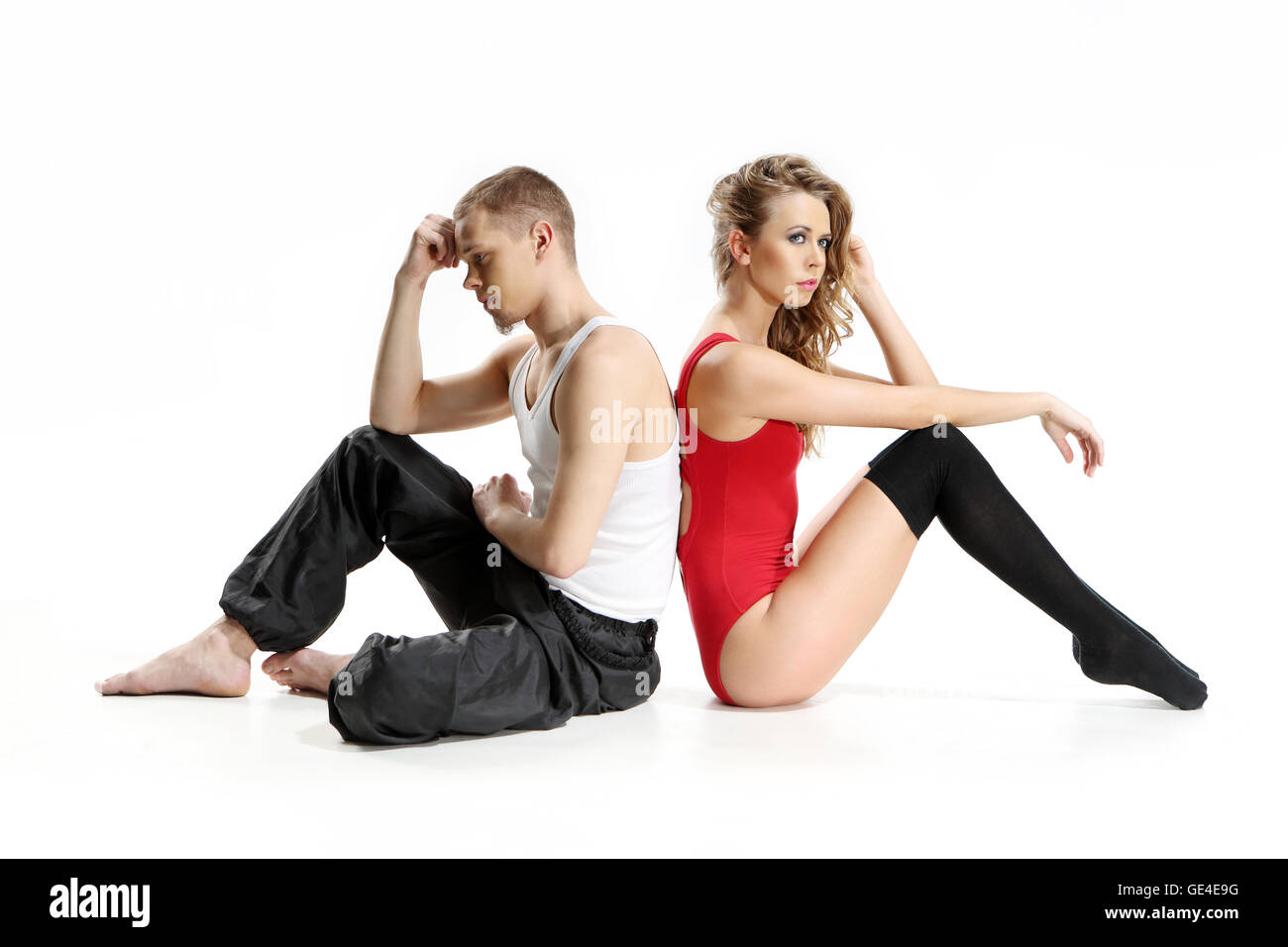 Unhappy couple of lovers, two disillusioned young dancers sitting back based on the sad pose. - Stock Image