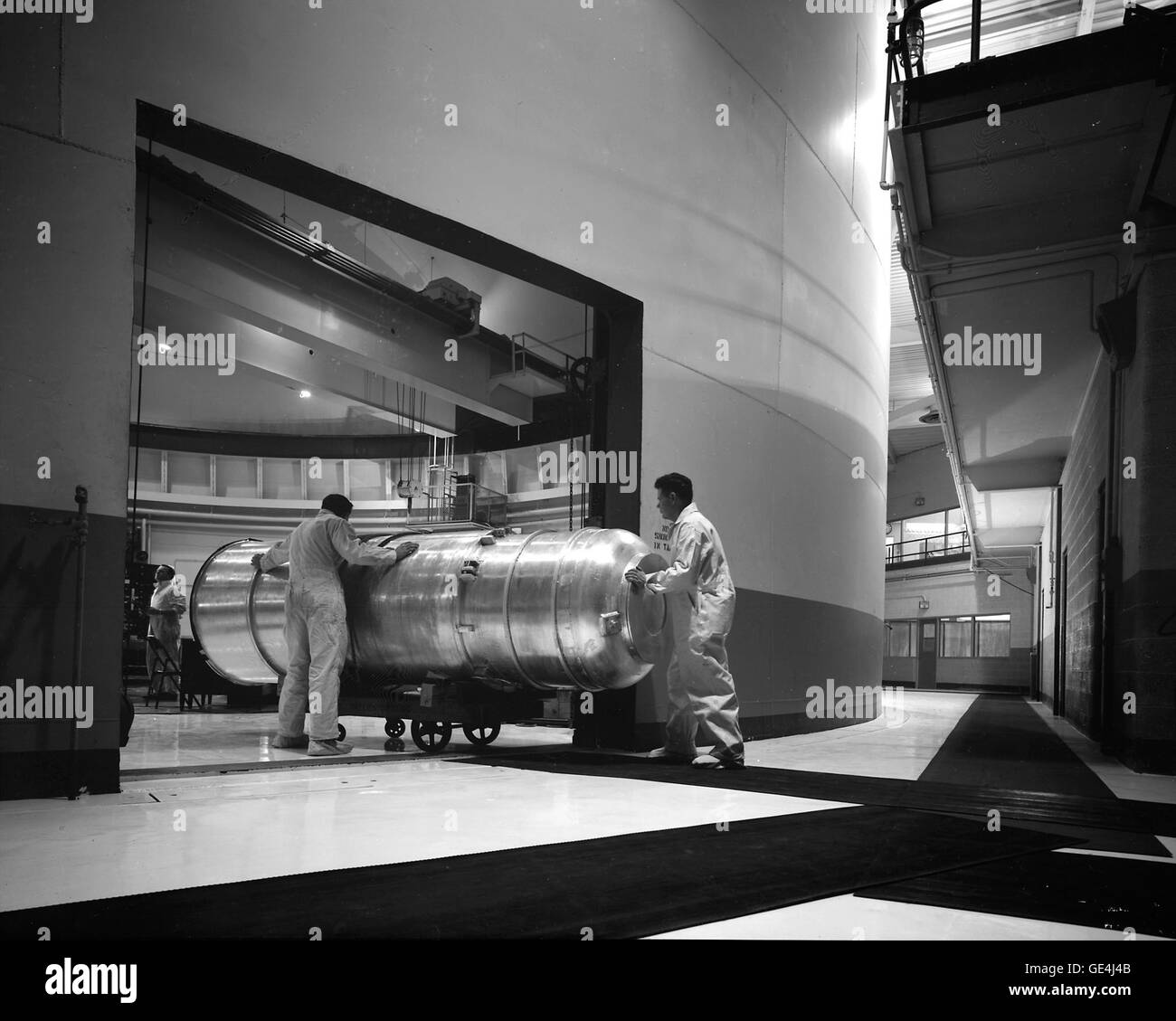 "Technicians wheel a large ""thimble"" containing experiments for irradiation into the containment - Stock Image"