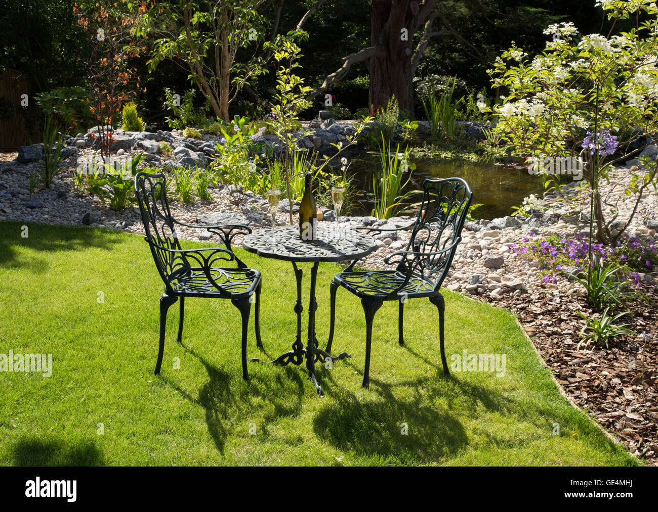a garden setting in full sun table chairs wine lawn and pond
