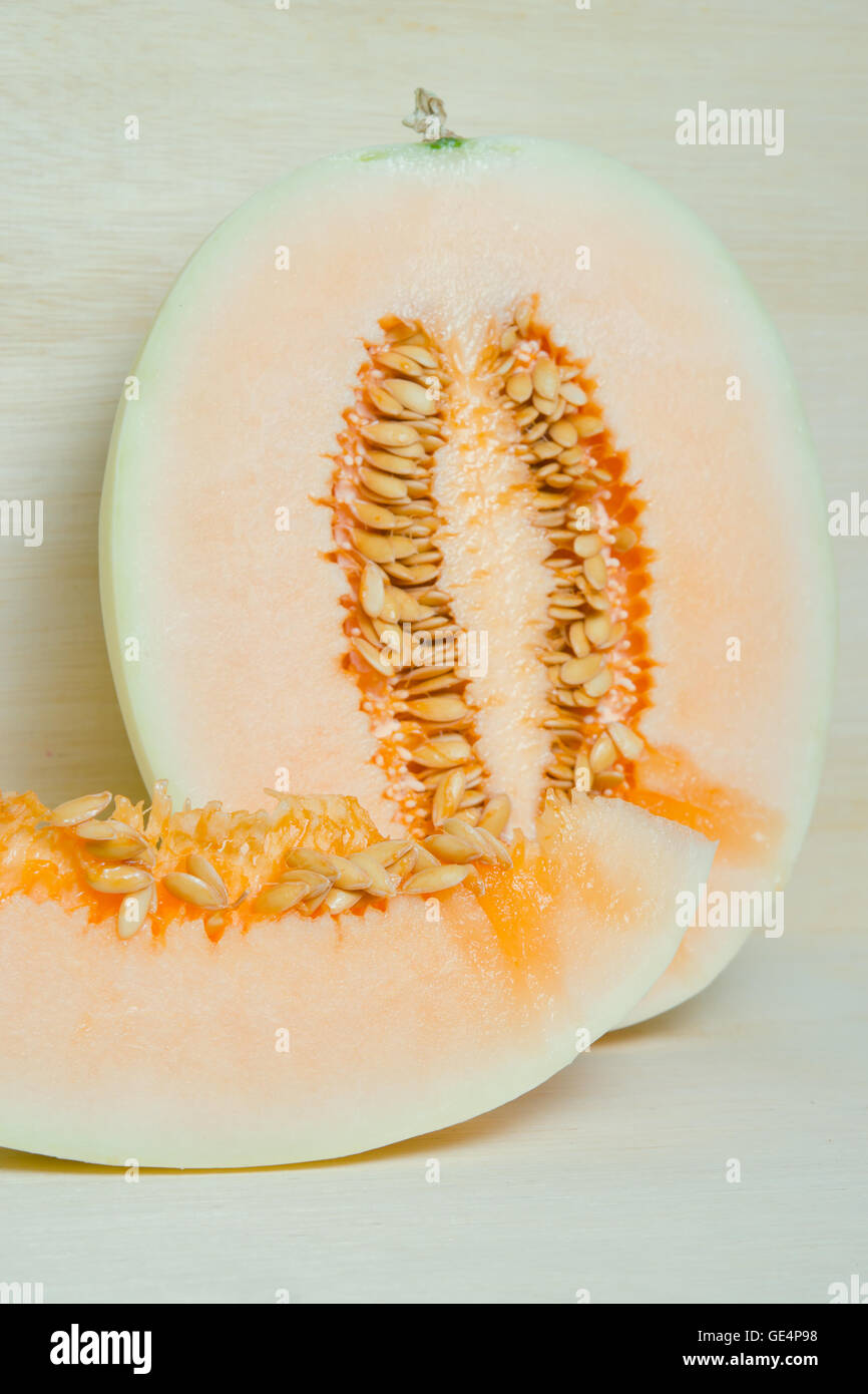 Sliced cantaloupe or Charentais melon or Cucumis melo var. cantalupensis on wooden board background - Stock Image