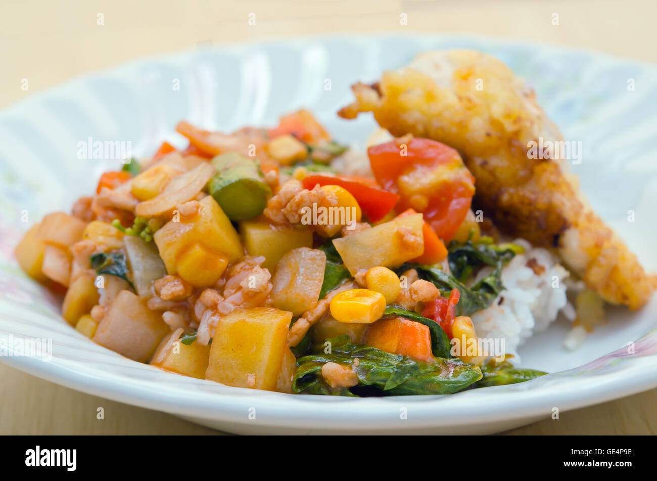 Fried chicken with vegetable tomato sauce and herb – thai home made food - Stock Image