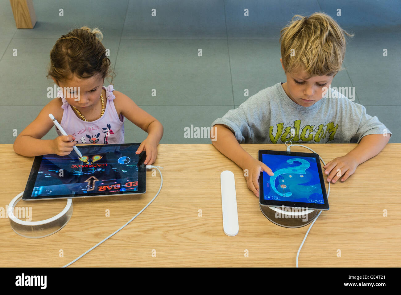Two children, 6-8 years old try out iPads at the Apple Store on State Street in Santa Barbara, California. - Stock Image