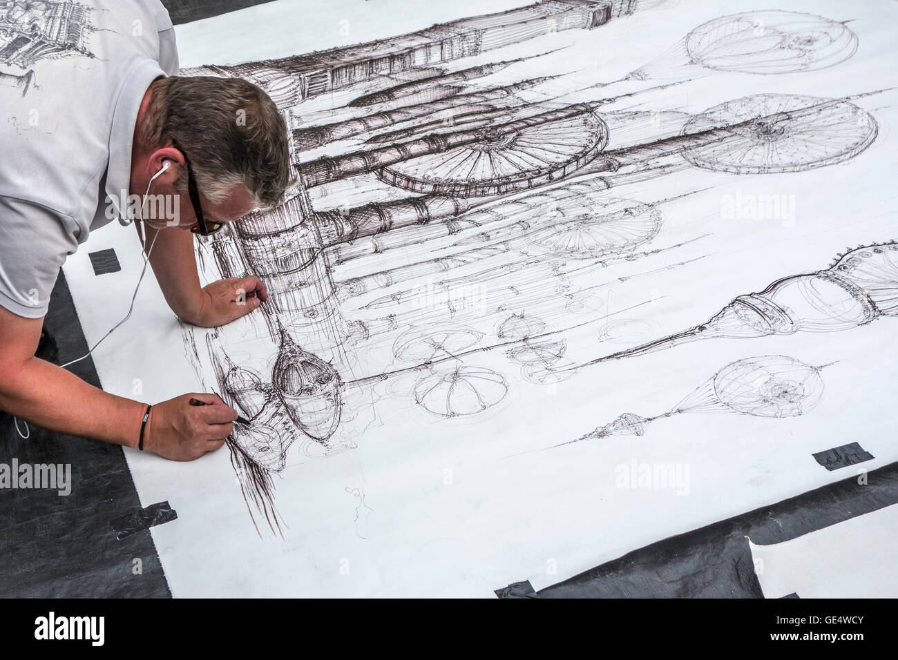 Street artist making fine detailed black and white drawing of imaginary machines on paper lying on the ground - Stock Image