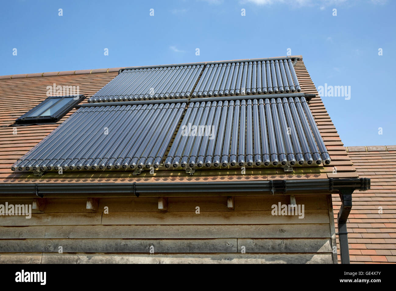 Array 80 solar thermal tubes barn roof Cotswolds UK - Stock Image
