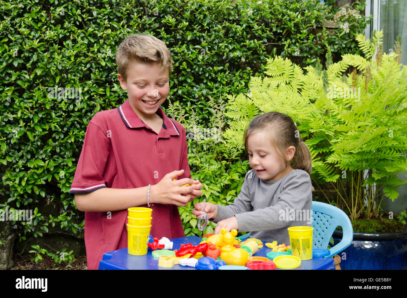 Three year old girl and ten-year-old boy, brother and sister, playing with Play-Doh modeling putty. UK. Outside - Stock Image