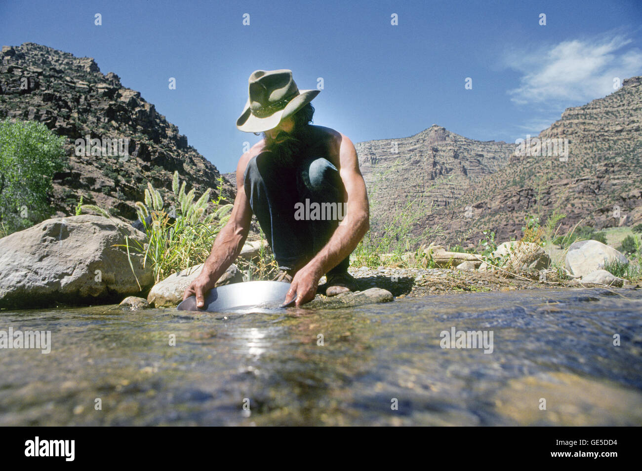 American hermit Nik Hougen pans gold from a small canyon streem in Desolation Canyon, Utah,  on the Green River. - Stock Image
