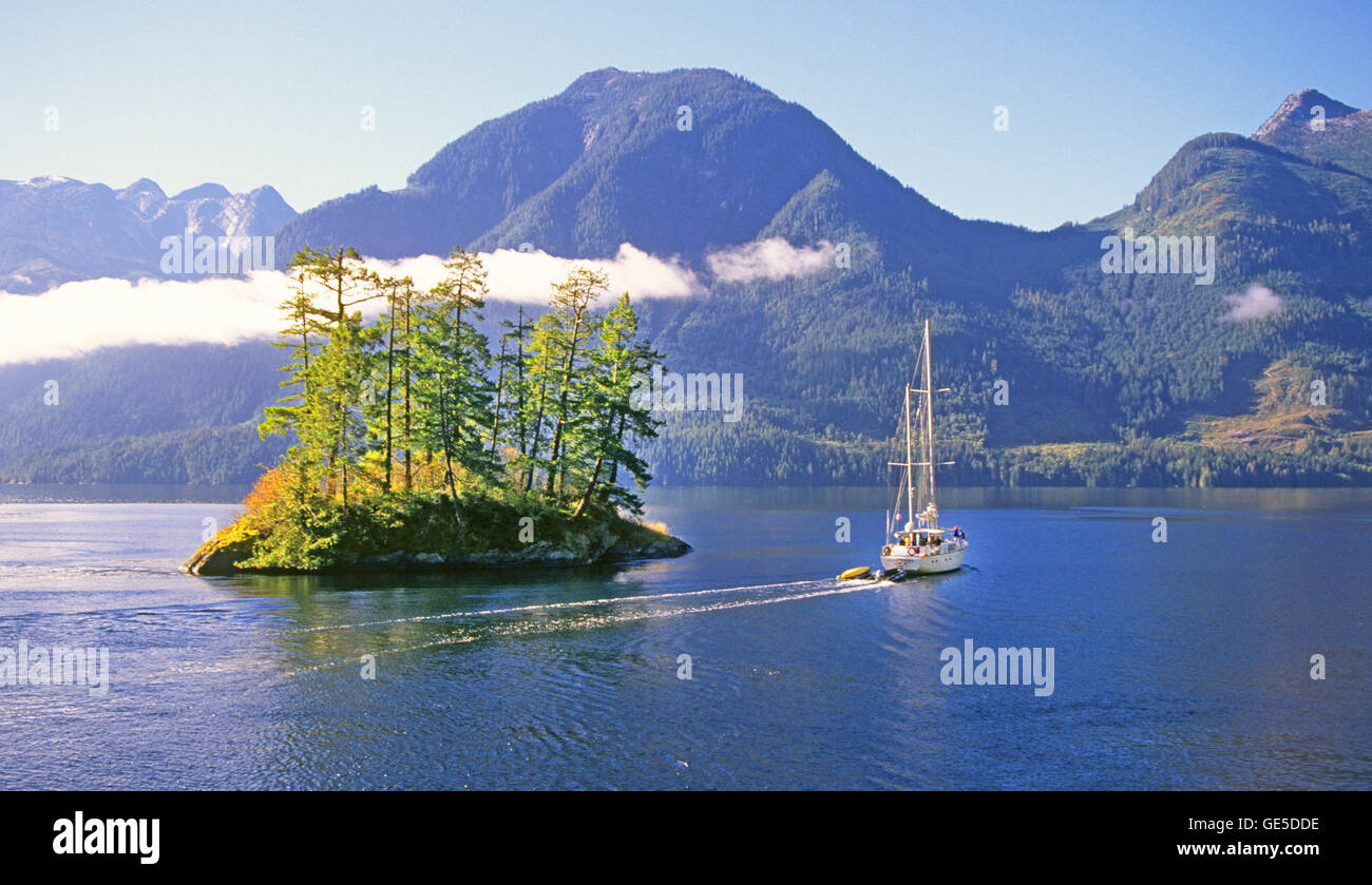 A sailboat navigates a narrow passage between islands in the Inside Passage in the Princess Louisa Inlet, British Stock Photo