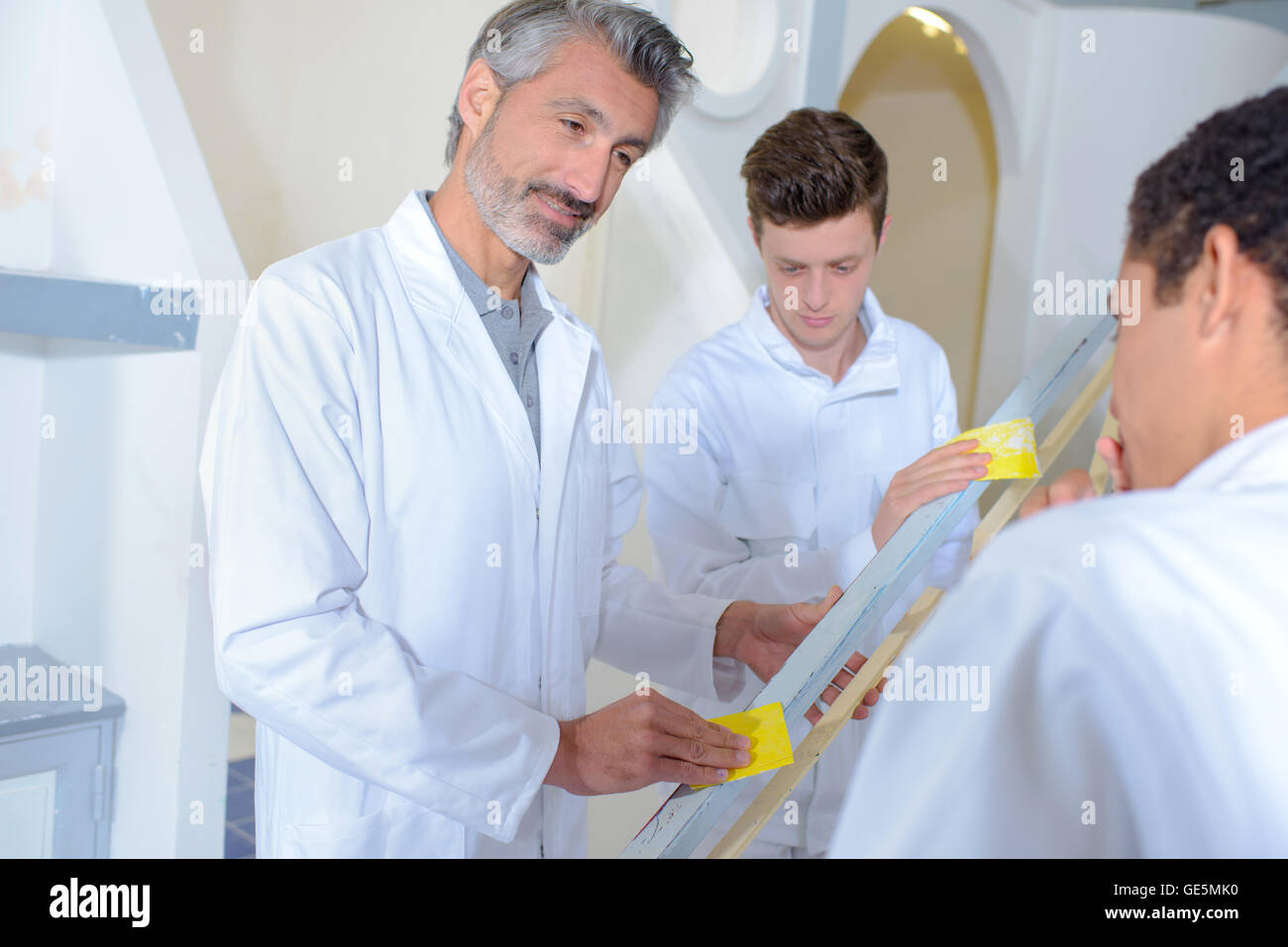 Teacher and student rubbing down a banister - Stock Image