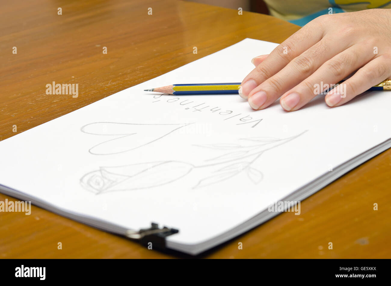 A girl is drawing a rose on a pile of paper for Valentine's event - Stock Image