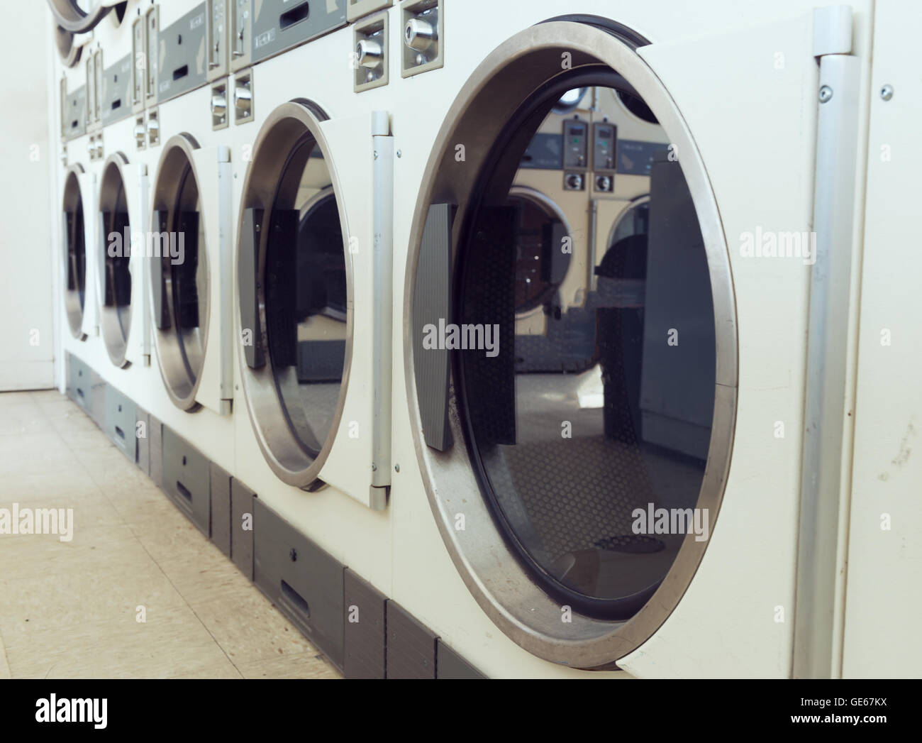 industrial laundry machines in laundrette - Stock Image