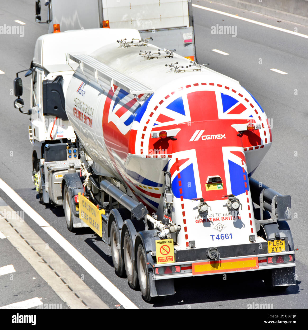 Cemex logistics bulk cement powder transport via articulated tanker lorry on UK motorway with Union Flag graphics - Stock Image