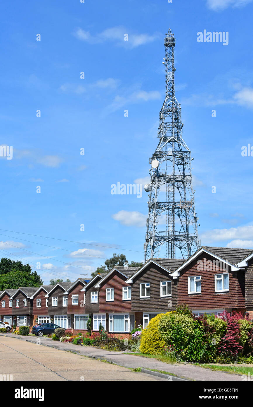 Tall phone and radio mast with satellite dishes towering over housing in residential suburban street Essex England Stock Photo