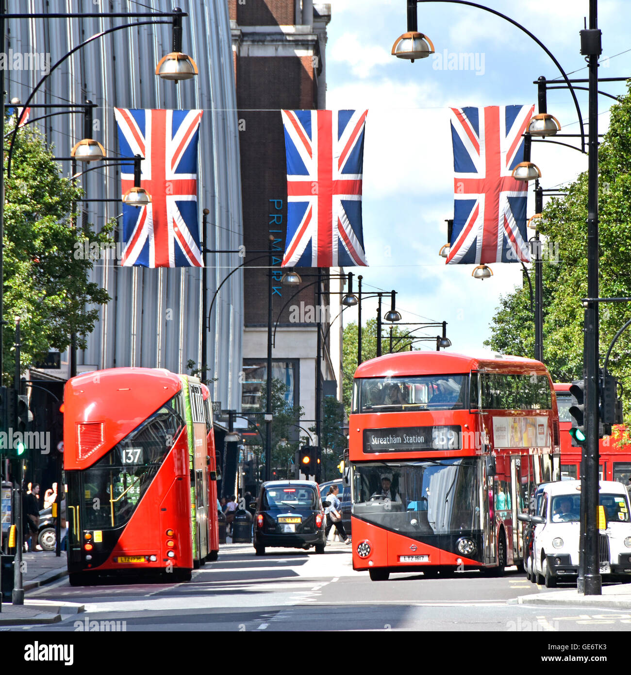 Oxford Street West End London England UK new red double decker Routemaster buses below Union Jack flags in this - Stock Image