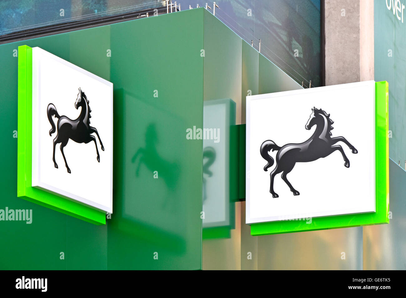 Close up twin black horse logo signs on corner fascia of Lloyds Bank plc branch building in London Oxford Street - Stock Image